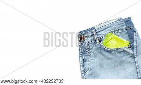 Menstruation Sanitary Pad In Light Green Packaging In Pocket Of Light Blue Jeans On White Background