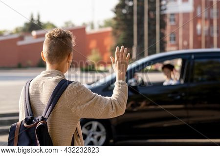 Schoolboy saying goodbye to his mom in the car before going to school in the morning