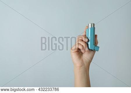 Female Hand Holds Asthma Inhaler On Light Gray Background