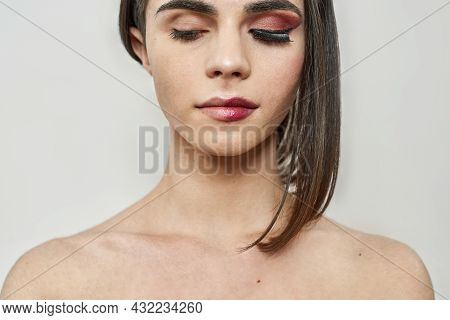 Close Up Of Young Transgender With Dark Night Party Makeup Applied On Half Of Face Posing Isolated O