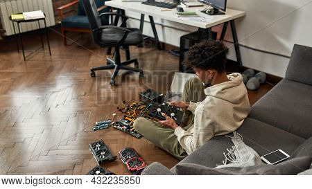Back Over Shoulder View Of African American Man Sit On Floor At Home Fix Upgrade Computer Hardware E