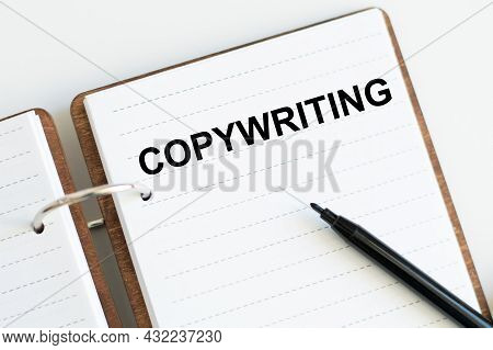 Notebook With Text Copywriting On The Table Next To A Black Marker
