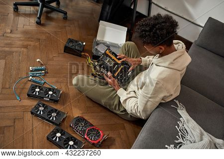 Top View Of African American Man Sit On Floor Check Hardware To Upgrade His Farm. Millennial Ethnic
