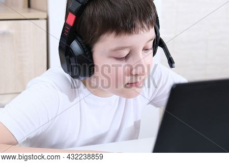 A Boy Homeschooler With Headphones Sitting At A Laptop And Learning, Online Education Concept