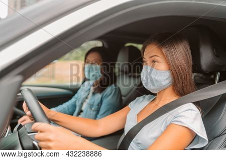 Car driving Asian woman wearing face mask inside during coronavirus pandemic. Driver with passenger on road trip drive.