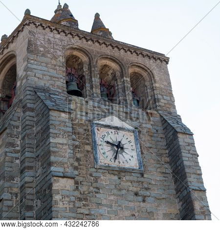 Stone Tower With Three Bells And A Beautiful Ancient Clock. Evora, Portugal, Europe