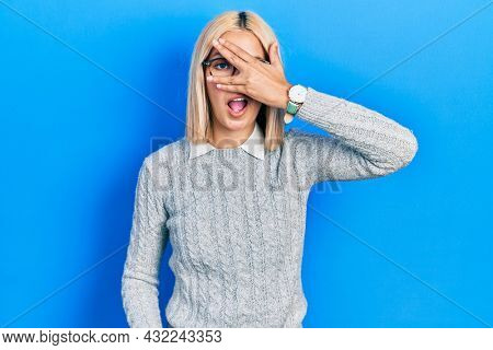 Beautiful blonde woman wearing glasses peeking in shock covering face and eyes with hand, looking through fingers with embarrassed expression.