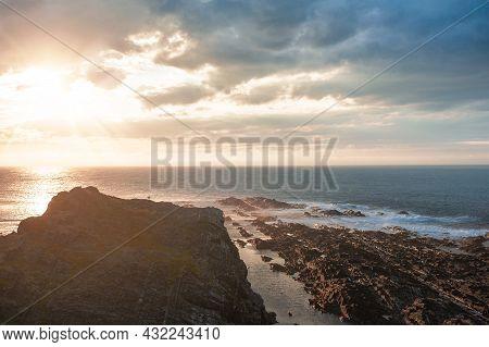 Dramatic Scene With Big Rocks, Sea, Sunbeam And Sundown