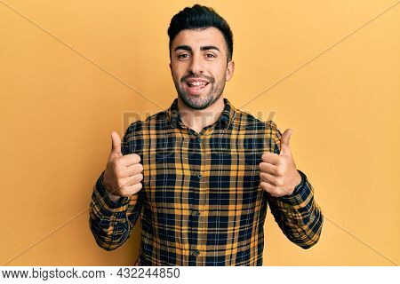 Young hispanic man wearing casual clothes success sign doing positive gesture with hand, thumbs up smiling and happy. cheerful expression and winner gesture.