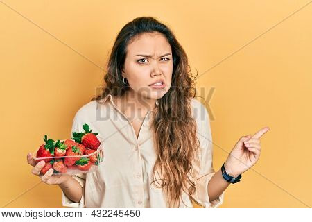 Young hispanic girl holding strawberries pointing aside worried and nervous with forefinger, concerned and surprised expression