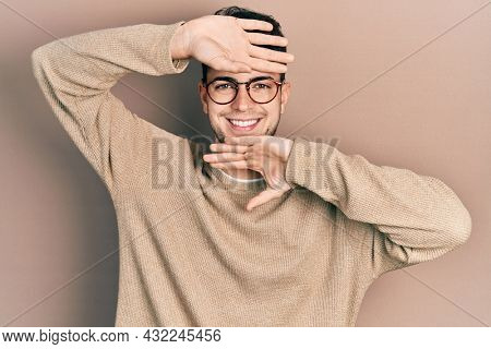 Young hispanic man wearing casual clothes and glasses smiling cheerful playing peek a boo with hands showing face. surprised and exited