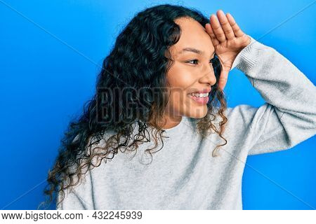 Young latin woman wearing casual clothes very happy and smiling looking far away with hand over head. searching concept.