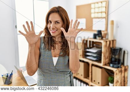 Middle age hispanic woman at the office showing and pointing up with fingers number ten while smiling confident and happy.