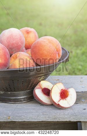 Cut Peach Sitting On A Bench Next To A Colander Of Whole Peaches Outside.