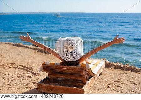 Beautiful Woman Sunbathing On A Beach At Tropical Travel Resort, Enjoying Summer Holidays Raising He