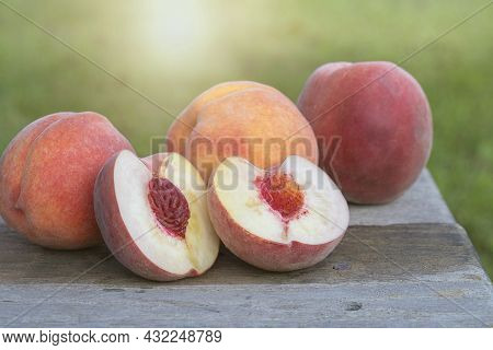 Fresh Cut Peach Sits On A Bench With Three Whole Peaches From The Orchard.