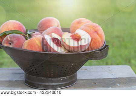 Freash Cut Peach With Whole Peaches In An Antique Colandar Outside.