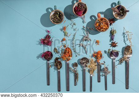 Assortment Of Dried Relaxing Tea Herbs In Spoons And Cups  On Blue Background. Calendula, Mint, Anis