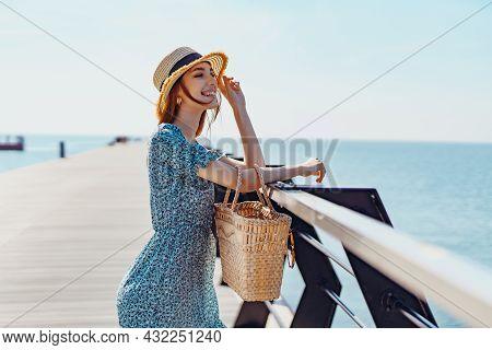 Beautiful Redhead Woman Posing At Sunny Day. Walks Along The Pier Near The Sea. Girl Wearing Fashion