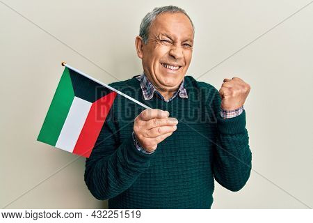 Handsome senior man with grey hair holding kuwait flag screaming proud, celebrating victory and success very excited with raised arm