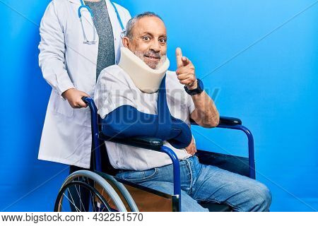 Handsome senior man with beard sitting on wheelchair with neck collar pointing fingers to camera with happy and funny face. good energy and vibes.