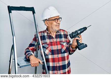 Handsome mature handyman holding screwdriver wearing hardhat by construction stairs smiling looking to the side and staring away thinking.