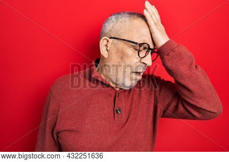 Handsome mature man wearing casual sweater and glasses surprised with hand on head for mistake, remember error. forgot, bad memory concept.