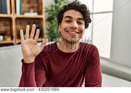 Young hispanic man smiling happy saying hello with hand at home.
