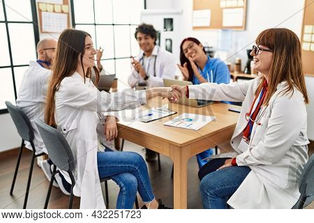Group of doctor smiling and clapping to partners handshake in a medical meeting at the clinic office.