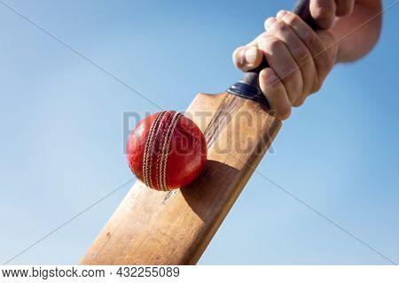 Cricket player batsman hitting a ball with a bat shot from below against a blue sky