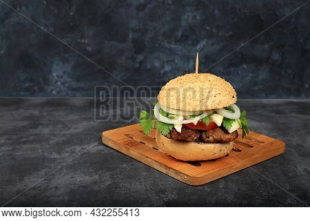 Cheeseburger With Fresh Parsley Leaves, Tomatoes, Cream Cheese, Onions And Cutlet On An Old Wooden B