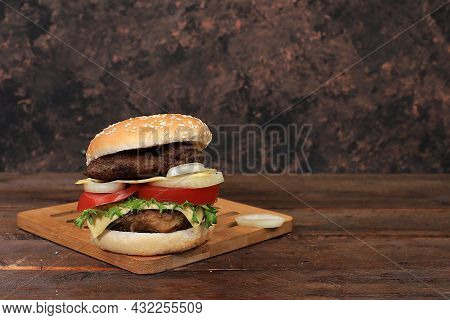 Cheeseburger With Fresh Parsley Leaves, Tomatoes, Cream Cheese, Onion And Cutlet On An Old Wooden Bo