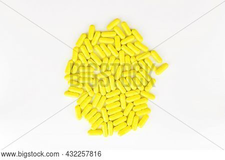 Yellow Pills Capsules Heap On White Background. Medicinal Concept. Top View. Flat Lay. Close Up. Sel