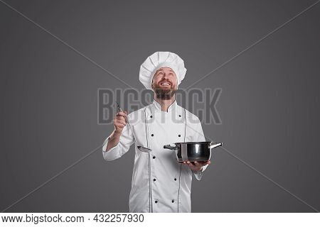 Delighted Bearded Male Chef With Ladle And Saucepan Smiling And Looking Up While Cooking Soup Agains