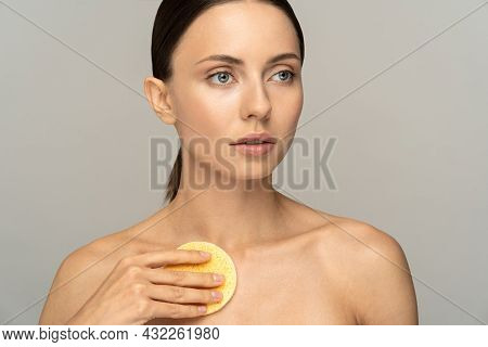 Young Woman With Nude Make-up And Naked Shoulders Cleaning Body With Exfoliating Sponge Isolated On
