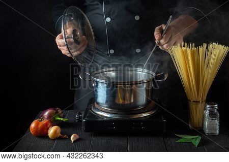 Cook Prepares Italian Pasta In A Saucepan With Vegetables. Close-up Of Cook Hands While Cooking In R