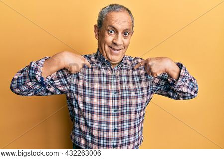 Handsome senior man with grey hair wearing casual shirt looking confident with smile on face, pointing oneself with fingers proud and happy.