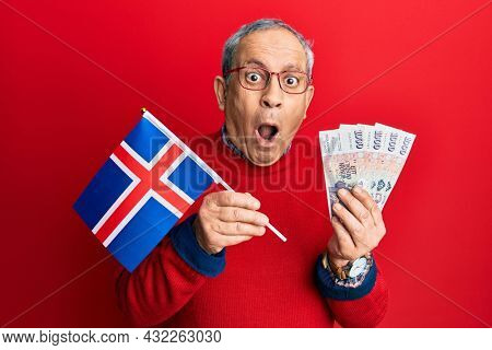 Handsome senior man with grey hair holding iceland flag and icelandic krona banknotes afraid and shocked with surprise and amazed expression, fear and excited face.