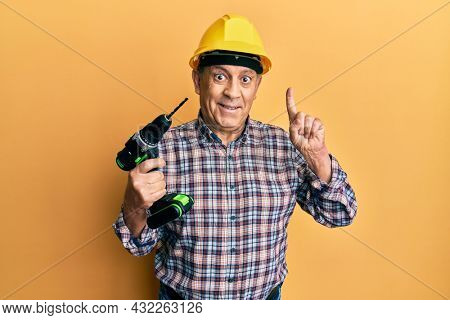 Handsome senior man with grey hair holding electric screwdriver wearing hardhat smiling with an idea or question pointing finger with happy face, number one