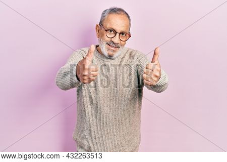 Handsome senior man with beard wearing casual sweater and glasses approving doing positive gesture with hand, thumbs up smiling and happy for success. winner gesture.