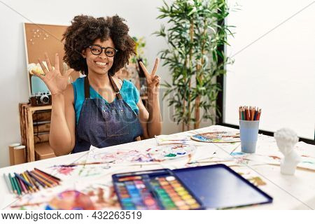Beautiful african american woman with afro hair painting at art studio showing and pointing up with fingers number seven while smiling confident and happy.