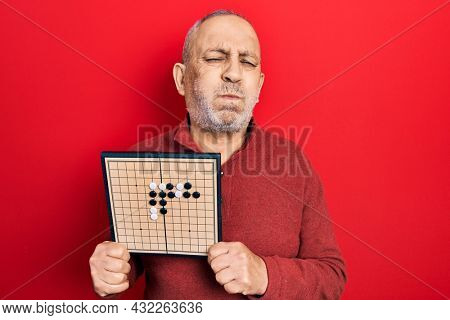 Handsome mature man holding asian go game board puffing cheeks with funny face. mouth inflated with air, catching air.