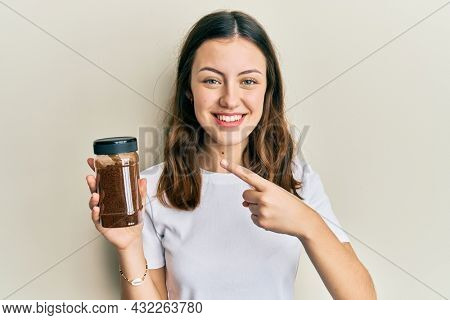 Young brunette woman holding soluble coffee smiling happy pointing with hand and finger