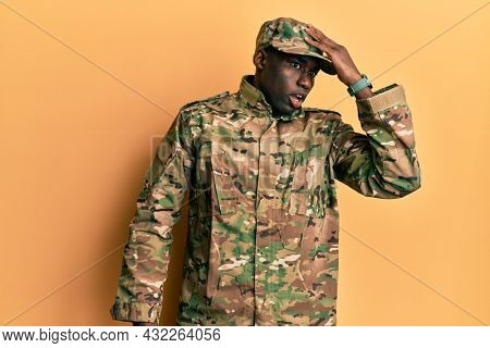 Young african american man wearing army uniform surprised with hand on head for mistake, remember error. forgot, bad memory concept.