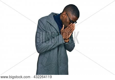 Young african american man wearing business clothes and glasses with sad expression covering face with hands while crying. depression concept.