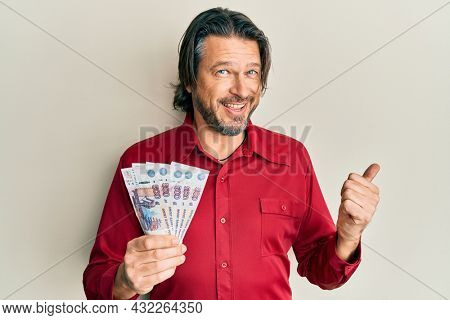 Middle age handsome man holding russian 500 ruble banknotes pointing thumb up to the side smiling happy with open mouth