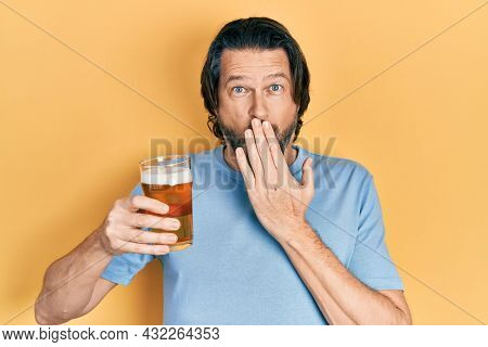 Middle age caucasian man drinking a pint of beer covering mouth with hand, shocked and afraid for mistake. surprised expression