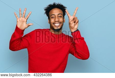 Young african american man with beard wearing casual winter sweater showing and pointing up with fingers number seven while smiling confident and happy.
