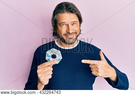 Middle age handsome man holding pill organizer pointing finger to one self smiling happy and proud