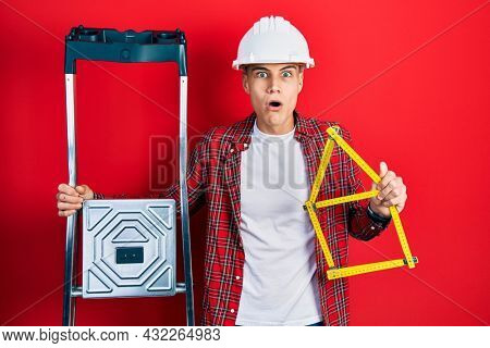 Young hispanic man wearing handyman uniform holding construction stairs and house project afraid and shocked with surprise and amazed expression, fear and excited face.